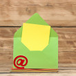 Stock Photo: E-mail symbol and colorful envelopes on old wooden background. c