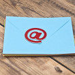 E-mail symbol and pile colorful envelopes on old wooden backgrou — Stock Photo