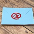E-mail symbol and pile colorful envelopes on old wooden backgrou — Stock Photo #34401235