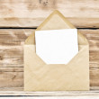 Blank postcard and envelope on old wooden background — Stock Photo