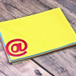 Stock Photo: E-mail symbol and pile colorful envelopes on old wooden backgrou