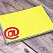 E-mail symbol and pile colorful envelopes on old wooden backgrou — Stock Photo #34409395