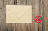 E-mail symbol and blank brown envelope on old wooden background — Stock Photo