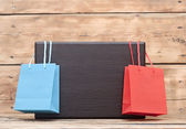 Colorful shopping bags and blank wood plate with copy space for — 图库照片