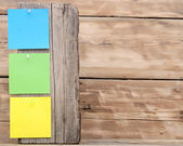 Colorful reminder notes attached on a old wooden signpost — Stockfoto