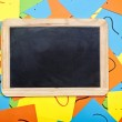 Blank chalkboard lying on a pile of colorful sticky notes with q — Stock Photo