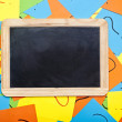 Blank chalkboard lying on a pile of colorful sticky notes with q — Stock Photo #34498287