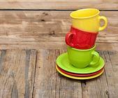 Farbenfrohe kaffeetassen auf holztisch — Stockfoto