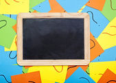 Blank chalkboard lying on a pile of colorful sticky notes with q — Stockfoto