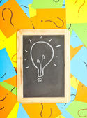 A lightbulb drawn on a chalkboard lying on a pile of colorful st — ストック写真