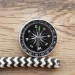 Marine rope and compass on wooden background — Stock Photo