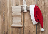 Wooden sign with Santa's hat and blank paper scroll on a wooden — Stock Photo