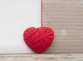 Heart made of red yarn hanging on cardboard background — Stok fotoğraf