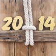 2014 year golden figures hanging by rope on wooden sign — Stock Photo