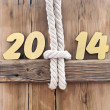 Stock Photo: 2014 year golden figures hanging by rope on wooden sign