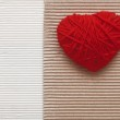 Heart made of red yarn hanging on cardboard background — Stock Photo #34855281
