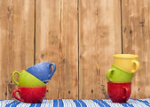 Colorful coffee cups on stripe tablecloth over wood background — Stock Photo