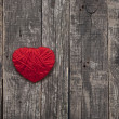 Stock Photo: Heart made of red wool yarn hanging on old wood background.