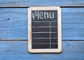 "Word ""menu"" writen on aged blackboard and hanging on wooden wall — Stockfoto"
