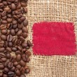 Coffee beans on old canvas with red patch  — Stock Photo