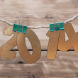 Two thousand fourteen New Year number decoration hanging on rope — Stock Photo
