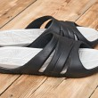 Black flip flops on wooden deck. summer background — Stock Photo #35828661
