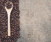 Roasted coffee beans and ground coffee in wooden spoon on coffee — Stock Photo