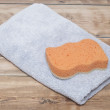 Sponge and towel on wood background — Stock Photo