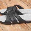 Black flip flops on wooden deck. summer background — Stock Photo