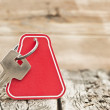 Key with a blank label on an old wooden plank — Stock Photo