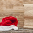 Santa hat and old paper scroll on wooden table — Stock Photo