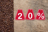 Twenty percent discount and coffee beans on a old burlap backgro — Stock Photo