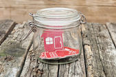 Shape home sign in a glass jar on wooden table — Stock Photo