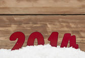 Year 2014 in fresh snow against wooden wall — Stock Photo