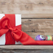 White boxs, red ribbon and christmas ball on wood background — Stock Photo #36779795