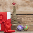 White boxs, red ribbon and christmas ball on wood background — Stock Photo #36779803