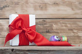 White boxs, red ribbon and christmas ball on wood background — Stock Photo