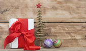 White boxs, red ribbon and christmas ball on wood background — Zdjęcie stockowe