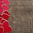 Pile red plastic heart-shape on canvas background — Stock Photo