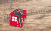 Symbol of the house with silver key on wooden background — Stock Photo