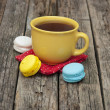 Colorful macaroon with a cup of coffee on old wooden background — Stock Photo