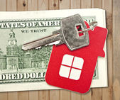 House keys and the hundred dollar banknotes on wooden table — Stock Photo