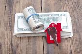 House keys over the hundred dollar banknotes against wooden back — Stock Photo