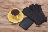 Mens wallet, gloves and coffee cup on wooden background — Stock Photo