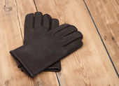 Pair of men's black leather gloves on wooden table top — Stock Photo