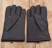 Pair of men's black leather gloves on wooden table top — 图库照片