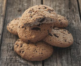 Oatmeal cookies with raisins on vintage wooden background  — Stock Photo