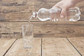 Water pour on to glass on wood table  — Stock Photo