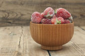 Frozen strawberries in a wooden bowl on wooden background  — 图库照片