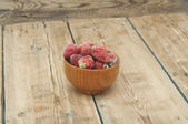 Frozen strawberries in a wooden bowl on wooden background  — Stockfoto